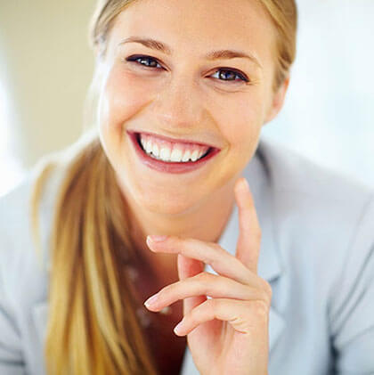 blonde woman with ponytail and white teeth smiling, holding hand up
