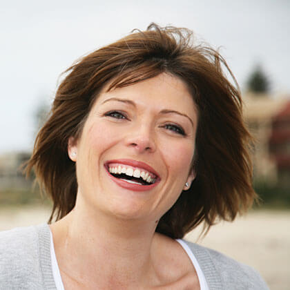 woman with short brown hair and bright white teeth smiling