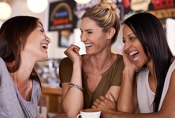 Three women with dental veneers smiling and laughing over coffee
