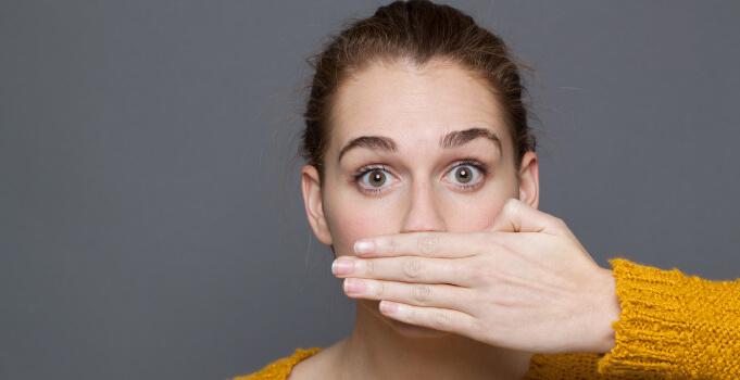 Woman covers mouth embarrassed of bad cavity